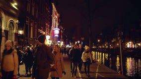 阿姆斯特丹,荷兰- 2017年12月27日 沿拥挤城市运河堤防走在晚上 库存图片