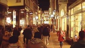 阿姆斯特丹,荷兰- 2017年12月28日 Crowded在晚上装饰了街道和店面 库存照片