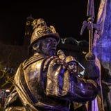 阿姆斯特丹,荷兰- 2015年12月19日:战士古铜色图在城市中心广场点燃了与街灯在晚上  图库摄影