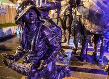 阿姆斯特丹,荷兰- 2015年12月19日:战士古铜色图在城市中心广场点燃了与街灯在晚上  免版税库存图片