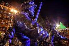 阿姆斯特丹,荷兰- 2015年12月19日:战士古铜色图在城市中心广场点燃了与街灯在晚上  库存图片