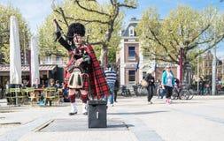 阿姆斯特丹,荷兰- 2017年4月31日:调整他的在街道的苏格兰吹风笛者仪器阿姆斯特丹佩带 免版税库存照片