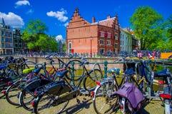 阿姆斯特丹,荷兰- 2015年7月10日:骑自行车停放沿着运行穿过城市的许多水道之一 免版税库存图片