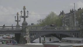 阿姆斯特丹/荷兰- 2019年4月:游船和桥梁在主要Gracht附近在阿姆斯特丹[平的外形] 影视素材