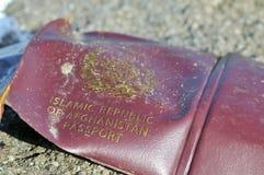 阿富汗护照离开在海滩由难民 库存图片