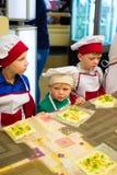 阿尔切夫斯克,乌克兰- 2017年10月15日:孩子的学校厨师咖啡馆的 准备果子薄饼 库存照片
