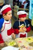 阿尔切夫斯克,乌克兰- 2017年10月15日:孩子的学校厨师咖啡馆的 准备果子薄饼 免版税库存照片