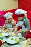 阿尔切夫斯克,乌克兰- 2017年10月15日:孩子的学校厨师咖啡馆的 准备果子薄饼 图库摄影