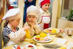 阿尔切夫斯克,乌克兰- 2017年7月16日:儿童` s在烹调土豆的大师类在烤箱用火腿和乳酪 库存图片