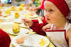阿尔切夫斯克,乌克兰- 2017年7月16日:儿童` s在烹调土豆的大师类在烤箱用火腿和乳酪 免版税图库摄影