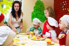 阿尔切夫斯克,乌克兰- 2017年7月16日:儿童` s在烹调土豆的大师类在烤箱用火腿和乳酪 免版税库存图片