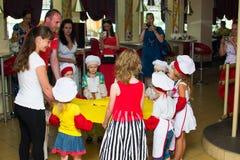 阿尔切夫斯克,乌克兰- 2017年7月16日:儿童` s在烹调土豆的大师类在烤箱用火腿和乳酪 图库摄影