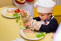 阿尔切夫斯克,乌克兰- 2017年7月30日:孩子的学校厨师 学会烹调面团用香肠 免版税图库摄影