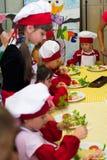阿尔切夫斯克,乌克兰- 2017年7月30日:孩子的学校厨师 学会烹调面团用香肠 免版税库存图片
