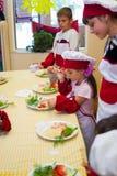 阿尔切夫斯克,乌克兰- 2017年7月30日:孩子的学校厨师 学会烹调面团用香肠 图库摄影
