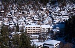 阿尔卑斯包括房子场面小的雪瑞士冬天森林 在一个晴朗的冬日期间,保加利亚的Shiroka Laka村庄 免版税库存照片