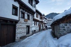阿尔卑斯包括房子场面小的雪瑞士冬天森林 沿Shiroka Laka村庄狭窄的街道,保加利亚在一个晴朗的冬日 图库摄影