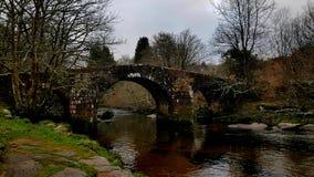 阿尔卑斯包括房子场面小的雪瑞士冬天森林 Hexworthy桥梁, Dartmoor,德文郡,英国 图库摄影