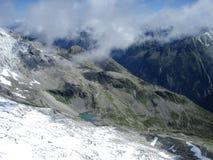 阿尔卑斯-山峰鸟瞰图与雪的在云彩 免版税库存图片