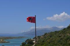 阿尔巴尼亚标志 在挥动在明亮的蓝天背景的旗杆的阿尔巴尼亚旗子 布特林特国家公园 免版税图库摄影