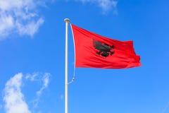 阿尔巴尼亚标志 在挥动在蓝天背景的杆的阿尔巴尼亚旗子 免版税库存照片
