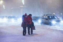 阿尔汉格尔斯克州,俄罗斯- 2017年1月22日:在重的夜冬天暴风雪的男人和妇女发怒路 不良视界,街道 库存图片