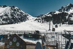 阿尔玛蒂,哈萨克斯坦滑雪电缆车,在麦迪奥的缆车客舱反对山背景的Shymbulak路线的 库存照片