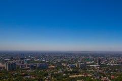 阿尔玛蒂从Koktobe小山,哈萨克斯坦的市视图 库存照片