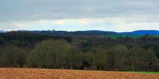 阿尔登风景,与空的冬天农田和森林和小山在一个雨天与黑暗的云彩 库存照片