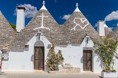 阿尔贝罗贝洛美丽的镇有trulli房子的在绿色植物和花,主要旅游区,普利亚地区,意大利中 免版税库存照片
