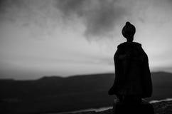 阿拉伯人剪影在沙漠和观看单独站立与雾云彩的日落  东部童话 免版税图库摄影