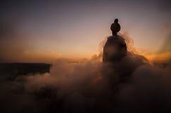 阿拉伯人剪影在沙漠和观看单独站立与雾云彩的日落  东部童话 免版税库存照片