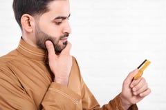 阿拉伯人在他的手保留金黄信用卡 免版税库存图片