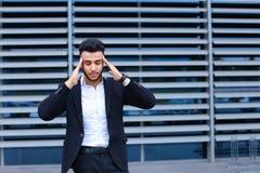 年轻阿拉伯人在商业中心显示疲倦的脖子痛 图库摄影