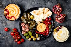 阿拉伯传统烹调 有皮塔饼的,橄榄, hummus中东meze盛肉盘,充塞了dolma, labneh在香料的乳酪球 免版税库存照片