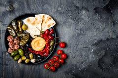 阿拉伯传统烹调 有皮塔饼的,橄榄, hummus中东meze盛肉盘,充塞了dolma, labneh在香料的乳酪球 库存照片