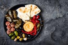 阿拉伯传统烹调 有皮塔饼的,橄榄, hummus中东meze盛肉盘,充塞了dolma, labneh在香料的乳酪球 免版税库存图片
