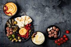 阿拉伯传统烹调 有皮塔饼的,橄榄, hummus中东meze盛肉盘,充塞了dolma, labneh在香料的乳酪球 图库摄影
