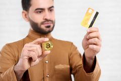 阿拉伯商人保留信用卡和一金黄bitcoin 库存照片