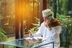 阿拉伯回教人用途巧妙的电话和在书写在咖啡店 免版税库存照片
