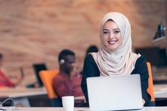 阿拉伯女商人佩带的hijab,运作在起始的办公室 库存图片