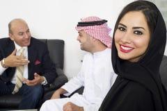 阿拉伯女实业家在有见面在背景中的买卖人的办公室 免版税图库摄影