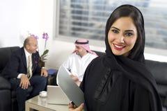 阿拉伯女实业家在有见面在背景中的买卖人的办公室 库存照片