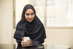 阿拉伯女实业家饮用的咖啡在办公室 免版税库存图片