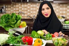 阿拉伯妇女佩带的hijab切口素食者在厨房里 免版税库存图片