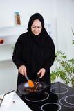 阿拉伯妇女在厨房里 图库摄影