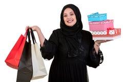 阿拉伯妇女在白色隔绝的运载的购物袋和礼物盒 免版税库存图片