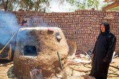 阿拉伯妇女烘烤面包在流浪的村庄 免版税库存照片