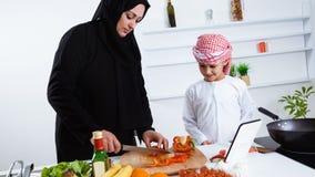 阿拉伯孩子在有他的母亲的厨房里 免版税库存照片