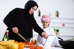 阿拉伯孩子在有他的母亲的厨房里 免版税库存图片